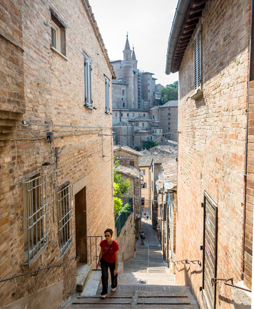 renaissance art: Urbino, Italy - August 13, 2015: street view with tourists in Urbino, Italy. The historic center of Urbino was represents the zenith of Renaissance art and architecture.