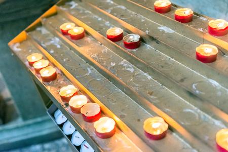 lighted wax candles detail inside a church, lighting and faith