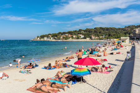 Antibes, France - June 26, 2016: people subathing on Plage de la Salis in Antibes. It is a popular local beach, a long stretch of fine, white sand curving around a protected bay.