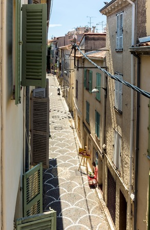 Antibes, France - June 27, 2016: day view of old town street with tourists in Antibes, France. Antibes is a popular seaside town in the heart of the Côte dAzur.