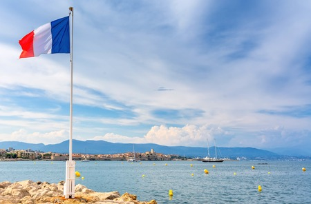 Antibes, France - June 29, 2016: view over the bay with France flag and alpes maritimes from Cap dAntibes, Antibes. Antibes is a popular seaside town in the heart of the Cote dAzur Stock Photo