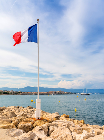 view over the bay with France flag and alpes maritimes from Cap dAntibes, Antibes. Antibes is a popular seaside town in the heart of the Cote dAzur