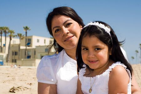 hispanic mother: a hispanic mother and daughter enjoying the sun on the sandy sunny beach