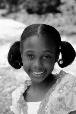 bw: a cute young african american girl with a smile in b&w