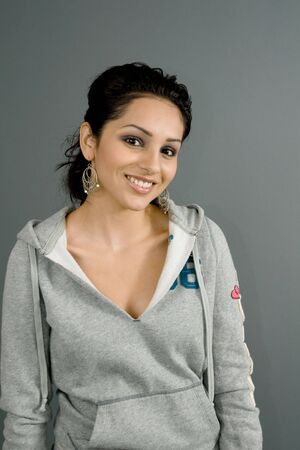 enticing: a young hispanic female smiles optimistically in a casual urban sweatshirt Stock Photo