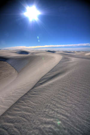 a line in the sand against bright blue sky and flaring sun Stock Photo - 5586167