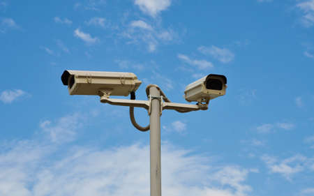 oversee: Two surveillance cameras mounted on the pole to oversee construction site Stock Photo