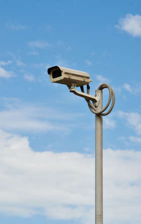 oversee: Surveillance camera mounted on the pole to oversee construction site Stock Photo