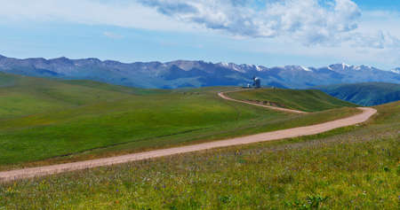 Asy Plateau and the road to the High-altitude Observatory at the background of Tien-Shan Mountains. Kazakhstan. Stock Photo