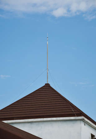 grounding: A lightning rod mounted on top of a building and electrically connected to the ground through a wire