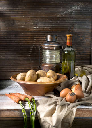 Still life whit vegetables carrots potatoes onions eggs old lamp