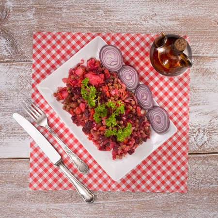 Russian beetroot salad vinaigrette White plate on checkered napkin on wood background Standard-Bild