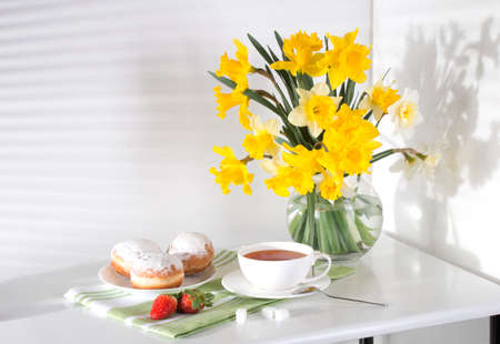 Still life with flowers daffodils white and yellow table towel green buns breakfast tea berry strawberry morning color from the window freshness Standard-Bild