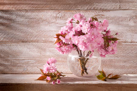Sakura flowers in a round vase on a wooden background still life beautiful gentle pink color