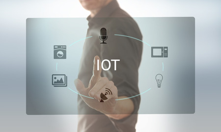 A man taps on a screen with icons on the subject of IOT Stock Photo