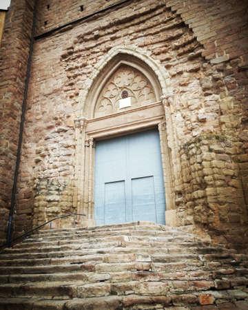 Entrance through the door in Romanesque stone church in medieval village Stock Photo