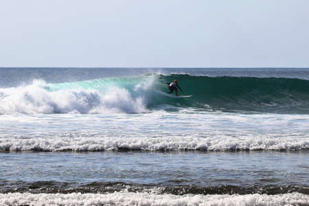 surfer rides on a wave on Bali