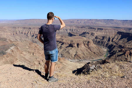 A man looks out over the Fish River Canyon - Namibia Africa Banco de Imagens