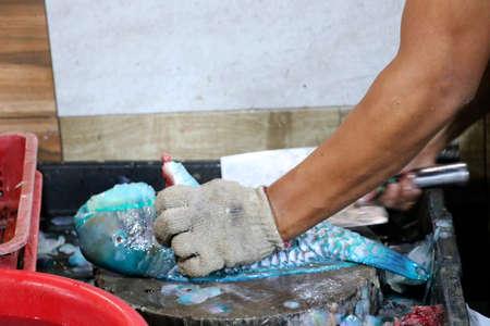 A man dismantles a fish at night market - Kota Kinabalu Borneo Sabah Malaysia Asia