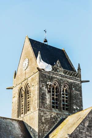 manequin: the famous church with the manequin of solder on the tower bell in St Mere Eglise in Normandy Stock Photo