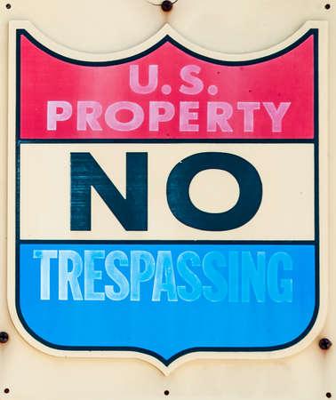 trepassing: Old no Trepassing Sign indicating US property Stock Photo
