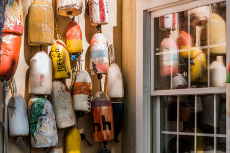 buoys: Old colorful lobster buoys against a weathered cedar shake wall.