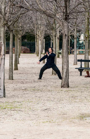 qigong: PARIS - MARCH 2: a man doing his exercise for oriental discipline in a park on March 2, 2014 in Paris France