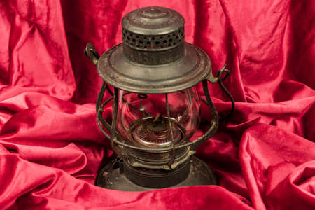 Old oil lantern isolated on red background
