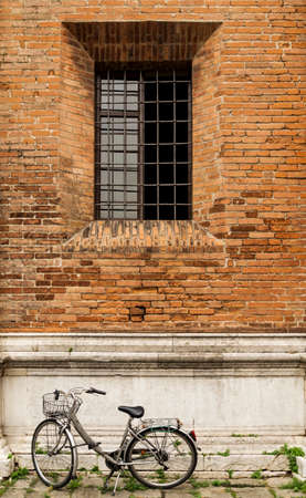 Old bicycle parked on a building wall in Ravenna, Italy Imagens