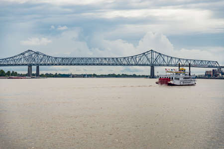 bridge over the Mississippi river with a boat in New Orleans, LA
