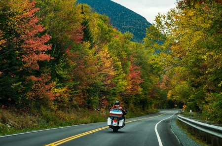 Motorcycle driving on the road on the White Mountains during the fall, New Hampshire, USA Фото со стока