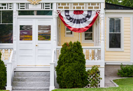 Exterior and Front Door of a Beautiful Old House with banting flag in New Hampshire, USA Editorial