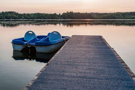 Row of Blue Pedal Boats during a sunset on an American lake
