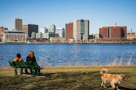 a couple with their dog enjoy the view of city skyline in Boston, Massachusetts, USA Stock Photo