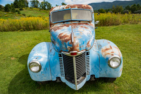 Old rusty blue truck abandoned ni a field in Stowe, Vermont USA