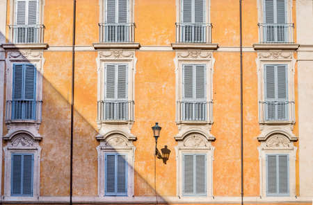 Stylish facade and windows of the traditional buildings in Rome, Italy