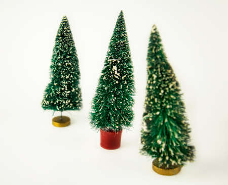 Three plastic Christmas tree on a white background