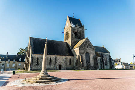 the famous church with the manequin of solder on the tower bell in St Mere Eglise in Normandy Stock Photo