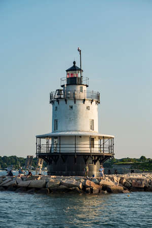 SOUTH PORTLAND ME - AUGUST 5: South Portland Breakwater lighthouse, also known as Bug light, guides a fishing trawler into the harbor. On August 5, 2018 in South Portland ME, USA