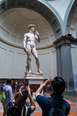 FLORENCE - JUNE 24: Tourists enjoy the vision of the David by Michelangelo inside the Accademia on June 24, 2018 in Florence, Italy Editorial