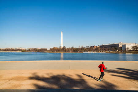 A photograph of the Washington Monument in Washington DC. A man is running near the pond. Stock Photo
