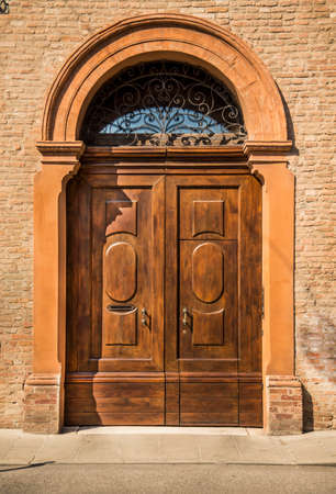 Old wooden red house door in the historical centre in Ferrara, Italy