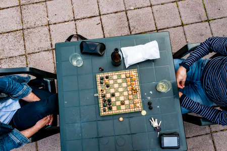 Adult people play chess game in a small town in Italy, reggio Emilia