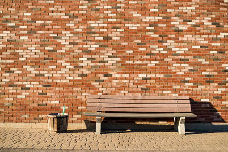 Wood bench and a red brick wall background in Wells in Maine USA Stock Photo