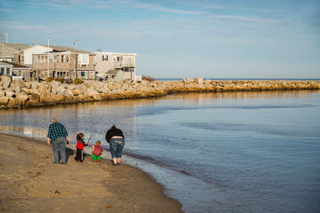 family with two kids walk on the ocean beach in Maine, USA