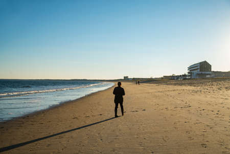 solitary old man walking on the beach in Maine USA