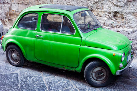 nice green Fiat 500 the italian city car. On a Street in Naples, Italy
