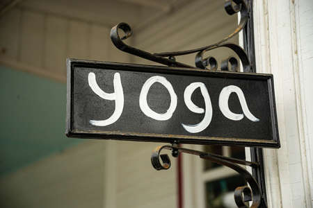 Closeup of a decorative yoga studio sign on the street promoting business in New England