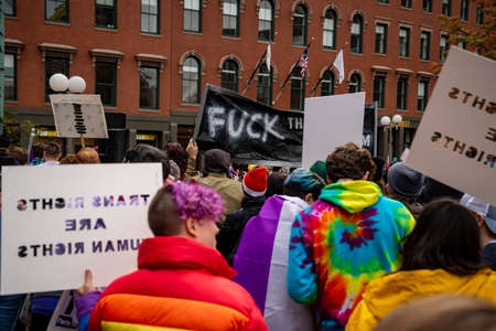 BOSTON, MASSACHUSETTS - OCTOBER 28, 2018: Protester marching for a peace pride rainbow flag at the Boston March for Our Lives political rally. Editorial