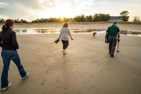 Family member are walking on a Beach At Sunset in Maine USA